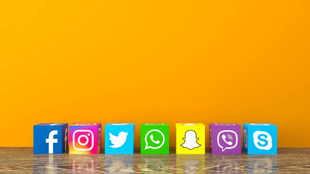 Social media services icons with on wooden desk with an orange color wall stock photo