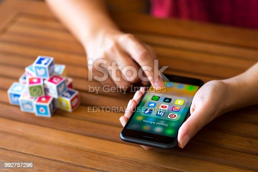 Antalya, Turkey - July 3, 2018: Woman using smart phone on a wooden desk. The smart phone is an iPhone 8. iPhone is a touchscreen smartphone developed by Apple Inc.