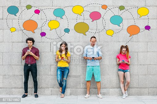 Social network concept. Young people texting with smart phones in front of big stone wall.