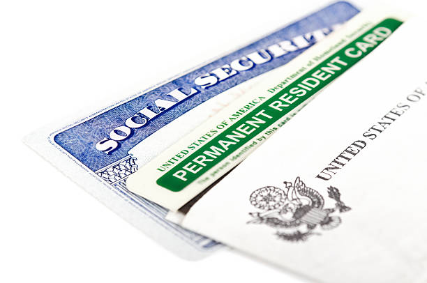 Social security and permanent resident card United States of America social security and green card on white background. Immigration concept. Closeup with shallow depth of field. green card stock pictures, royalty-free photos & images