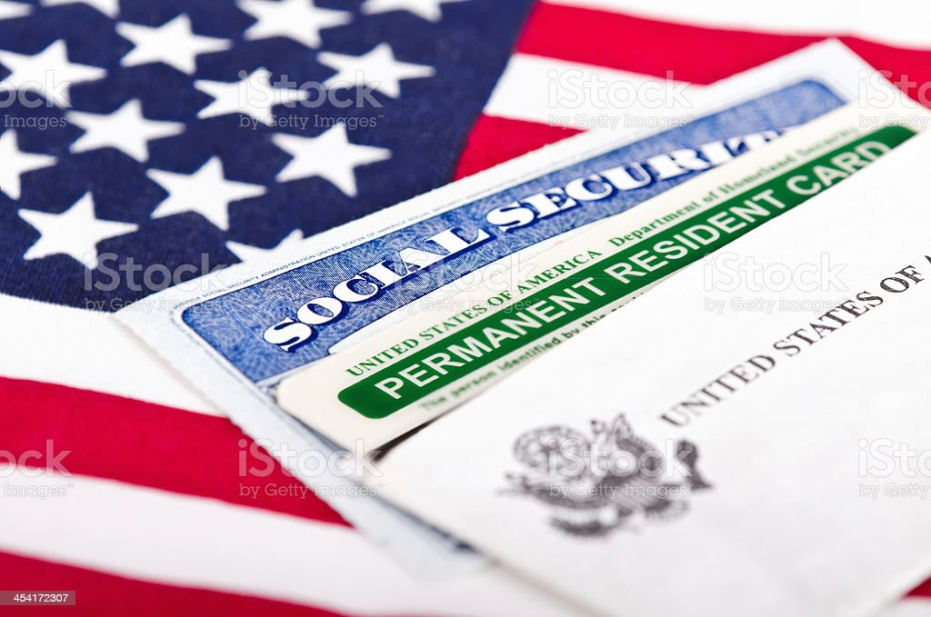 Social Security card and permanent resident on USA flag stock photo