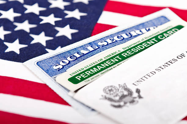 Social Security card and permanent resident on USA flag United States of America social security and green card with US flag on the background. Immigration concept. Closeup with shallow depth of field. green card stock pictures, royalty-free photos & images