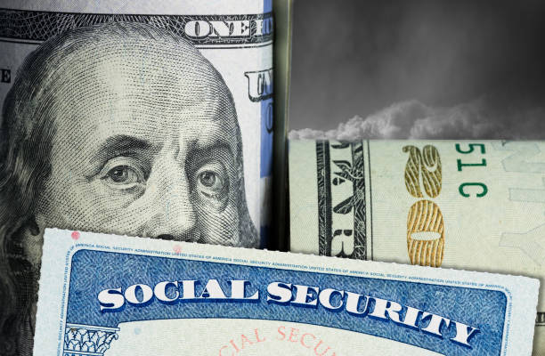 Social Security Card in front of Benjamin Franklin on dollar note stock photo