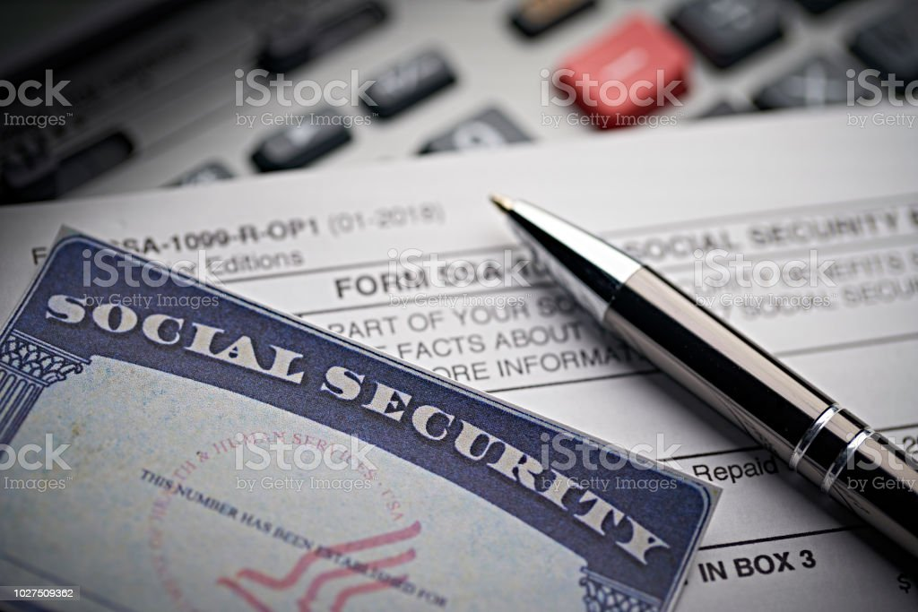 Social Security Card On Calculator With Pen Stock Photo