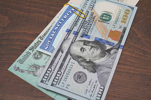 social security card, treasury check and usa 100 dollar bills - social security check stock photos and pictures
