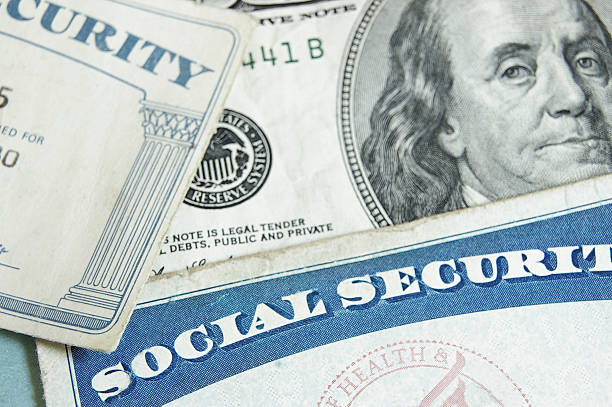 Social security cards angled on top one hundred dollar bill social security cards and US money - retirement concept social security stock pictures, royalty-free photos & images