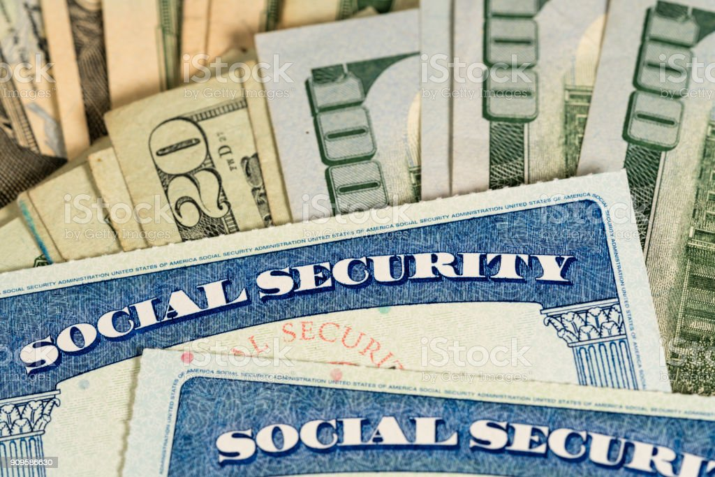 USA Social security cards laid on dollar bills USA Social security cards laid on pile of dollar bills to illustrate money in retirement Budget Stock Photo