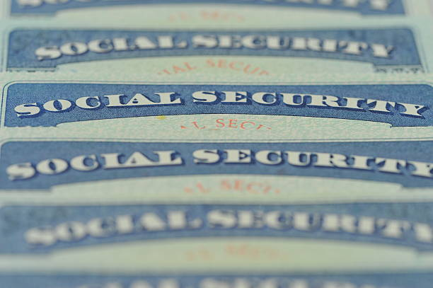 Social Security Cards Close-up of American Social Security cards. Selective focus, Blur. social security stock pictures, royalty-free photos & images