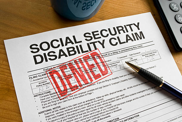 Social Security Claim Denied on a desk Denied rubber stamped on a social security disability claim. social security stock pictures, royalty-free photos & images