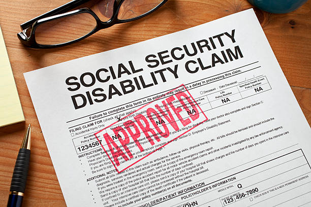Social Security Disabilty form stamped APPROVED. Approved Social Security Disability Claim Form on a desktop social security stock pictures, royalty-free photos & images