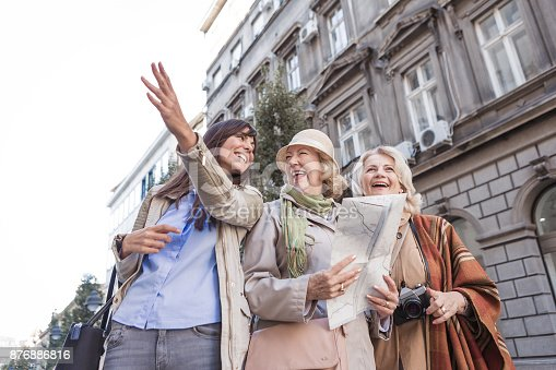 istock Social Seniors. Active seniors ladies traveling, exploring the city, looking at map, asking young woman, passenger for directions 876886816