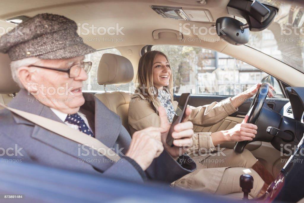 Sozialer Senioren. Großvater und Enkelin mit dem Auto fahren. Er ist Mobiltelefon verwenden. – Foto
