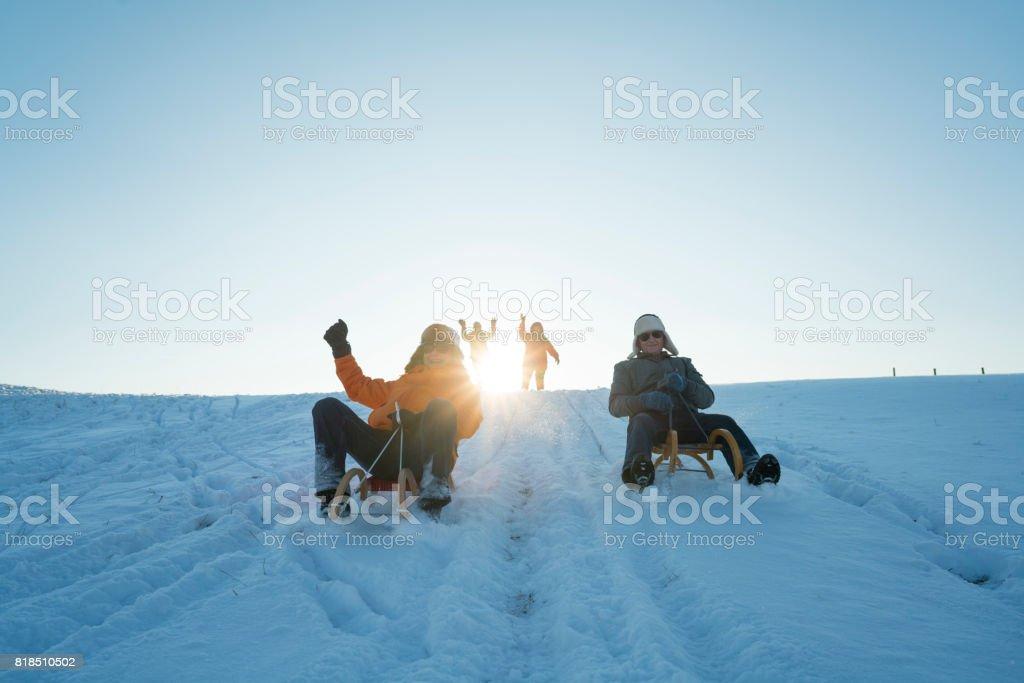 Social Seniors, tobogganing on sunny winter day stock photo