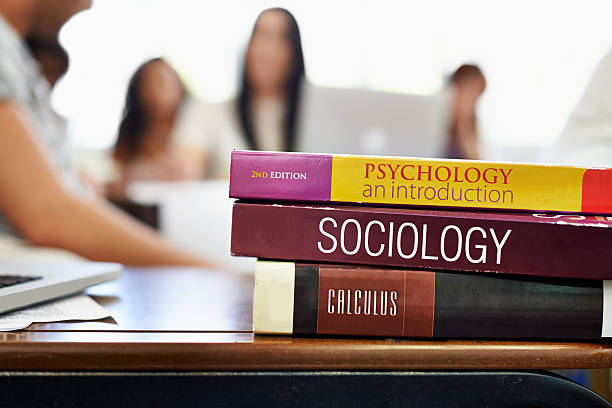 Social Studies Cropped shot of university text books on a desk with students blurred in the background textbook stock pictures, royalty-free photos & images