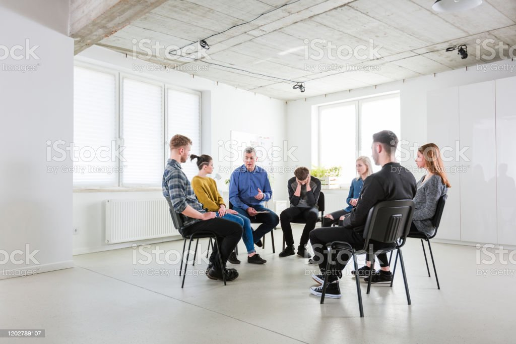 Social worker assisting students in lecture hall Social worker assisting young university students in lecture hall. Group of people are having mental health therapy session. They are discussing problems. 18-19 Years Stock Photo