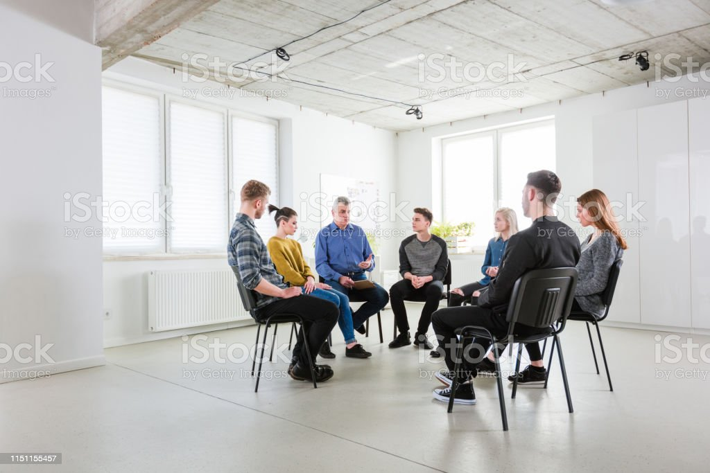 Social worker discussing problems with students Mental health therapist discussing problems with male and female students. Social worker is explaining young men and women in lecture hall. They are in group therapy at university. 18-19 Years Stock Photo