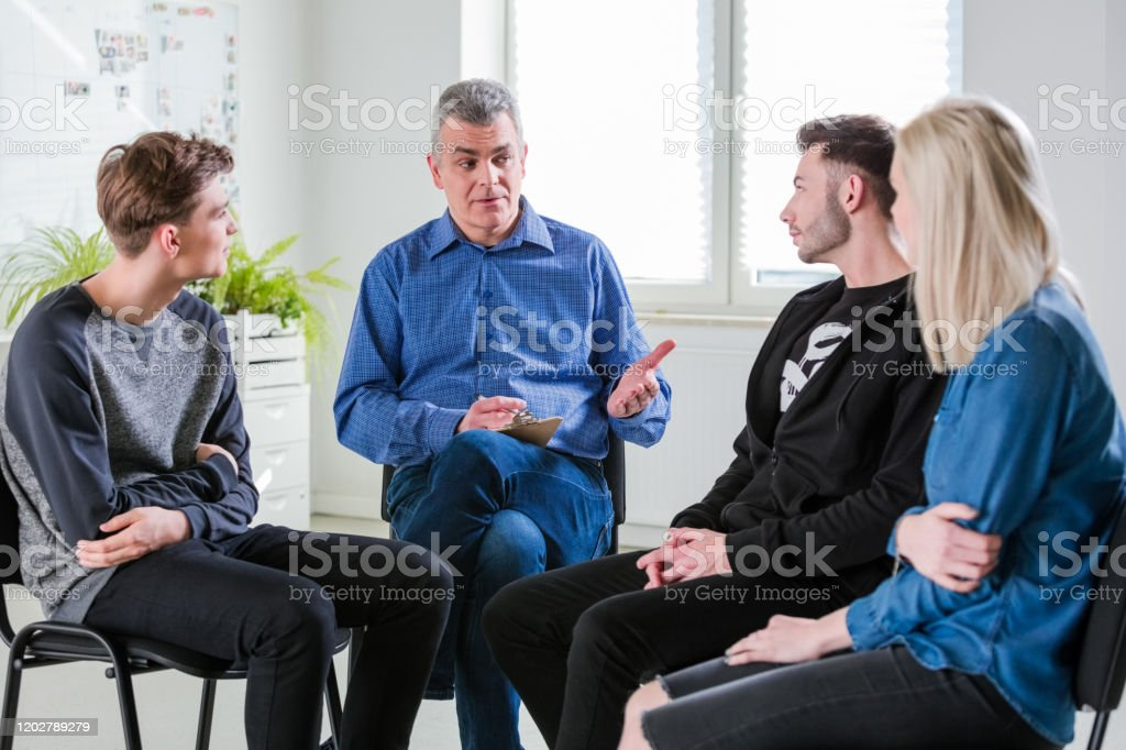 Social worker discussing problems with students Mental health therapist discussing problems with male and female students. Social worker is explaining young men and woman in lecture hall. They are in group therapy at university. 18-19 Years Stock Photo