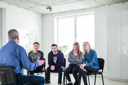 Social Worker Interacting With Depressed Students Stock Photo - Download Image Now