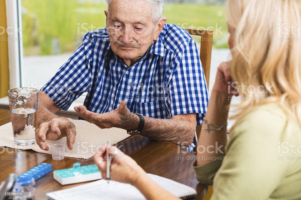 Social worker making notes as senior man taking his medicine royalty-free stock photo
