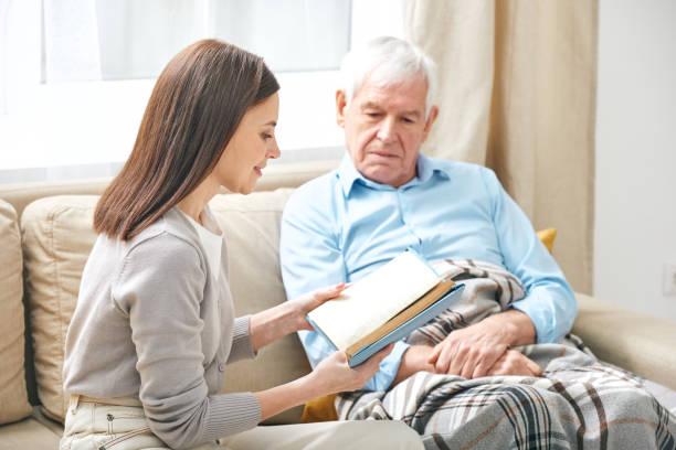 Social worker reading book to elderly man stock photo