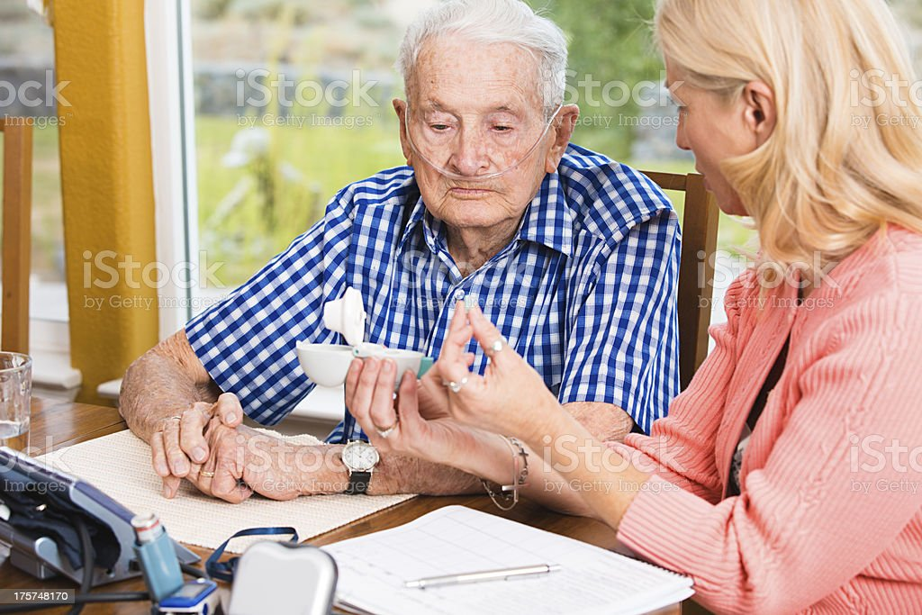 Social worker teaching senior man how to use medical equipment stock photo
