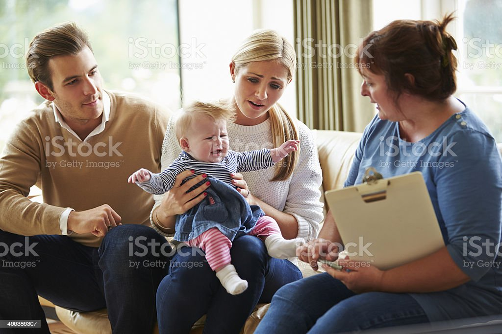 Social Worker Visiting Family With Young Baby stock photo