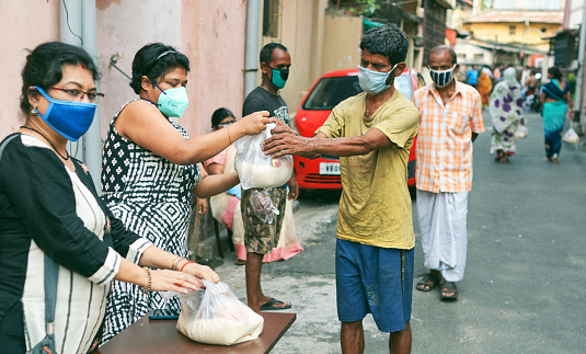 Civic volunteers of a social welfare association helping poor people by giving them grocery items like rice, pulses etc. during lockdown period in Kolkata. People are seen waiting in line. All of them are seen wearing face masks / cloths as a preventive measure. Shot at Lansdowne, Kolkata on 05/10/2020.