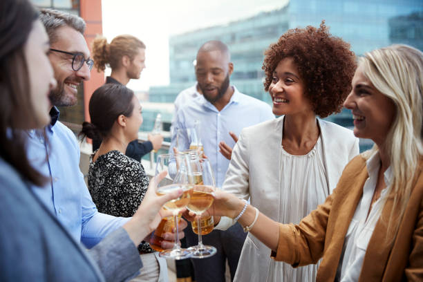 socialising office colleagues raising glasses and making a toast with drinks after work - happy hour stock photos and pictures