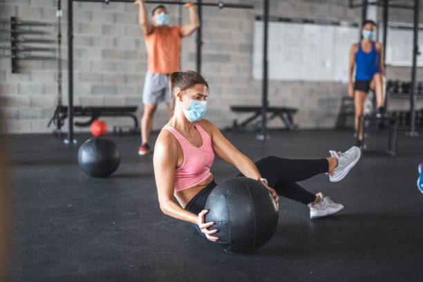 Socially Distanced Athletes in Masks Working Out at Gym stock photo