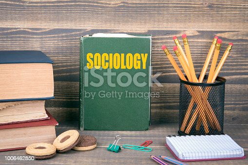 1190039622istockphoto Sociology concept. Book on a wooden background 1006462850