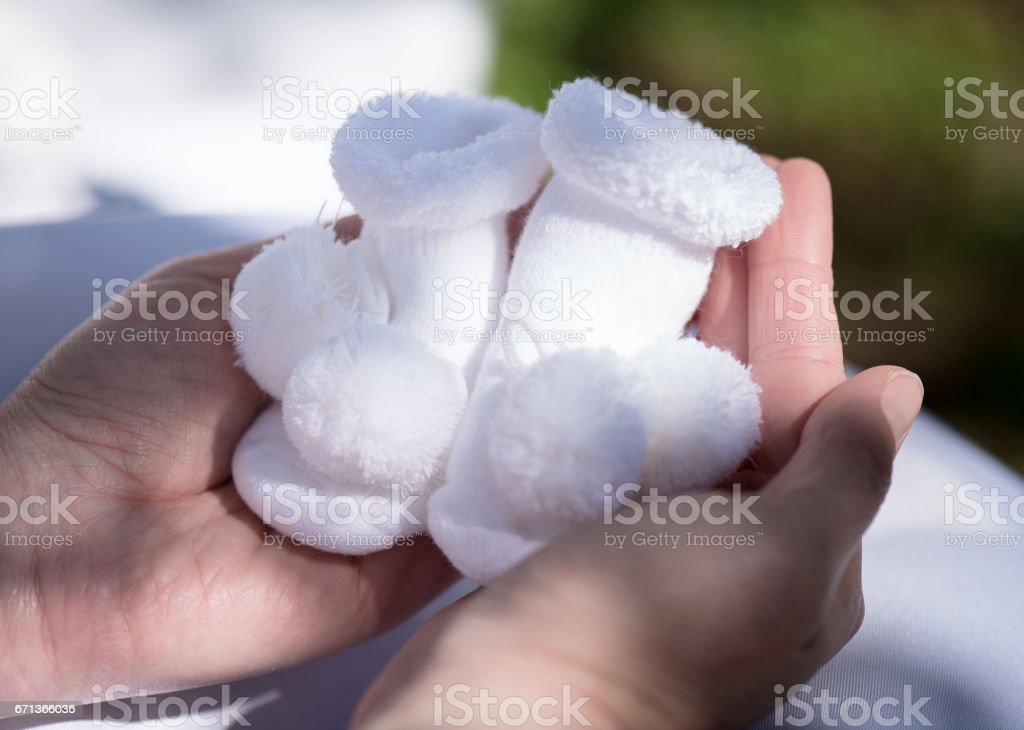 Socks for newborn in mother's hands.                            Black and white. stock photo