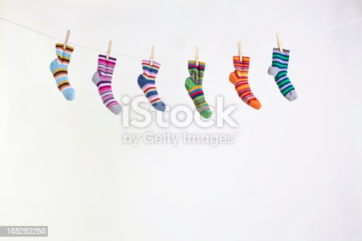 six different color socks hang on rope grafted with clothespin