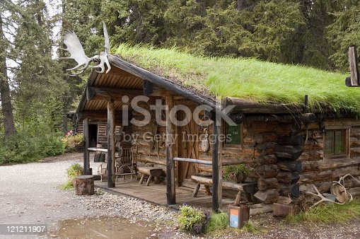 A sod roof log cabin at an Athabascan Village on the Chena River - Fairbanks, Alaska features a moose antlers over the doorway.