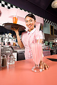 A studio image in a 1950, 1960s era soda shop with a waitress serving you a milkshake.  Click to view similar images.