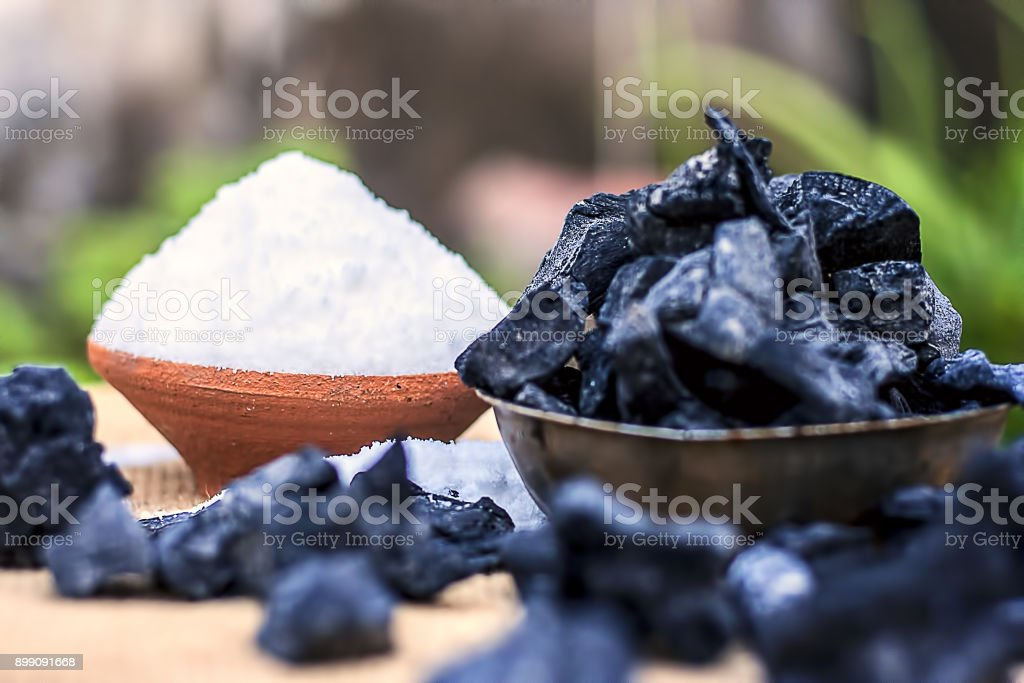 Sodium chloride,Salt in a clay bowl with coal. stock photo