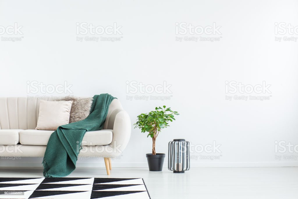 Sofa against empty wall stock photo