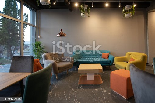Colorful Sofa and armchair in modern cafeteria, with pillows, coffee table, no people