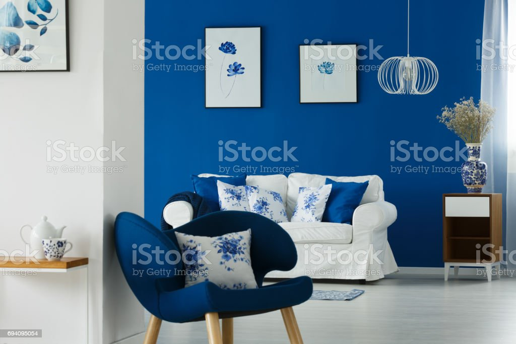 Sofa and chair with flowery pillows stock photo