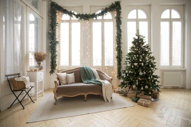 Sofa and Christmas tree near windows stock photo