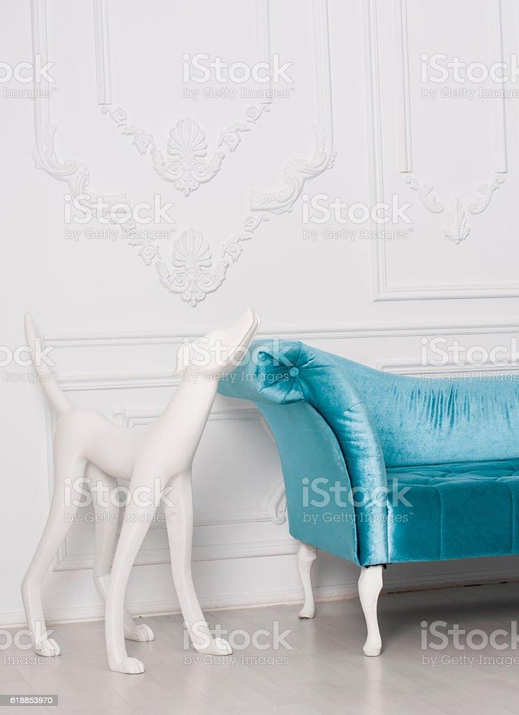 sofa armrest with white sculpture of dog stock photo