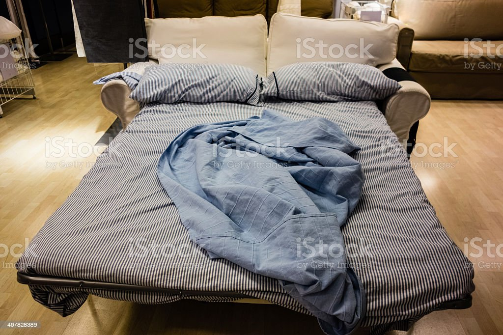 Sofa bed pulled out with blanket on it stock photo