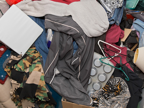 Close-up color photo of messy pile of household items including hangers, muffin tins, binder, jacket, blanket and clothes almost completely covering couch. Copy space.