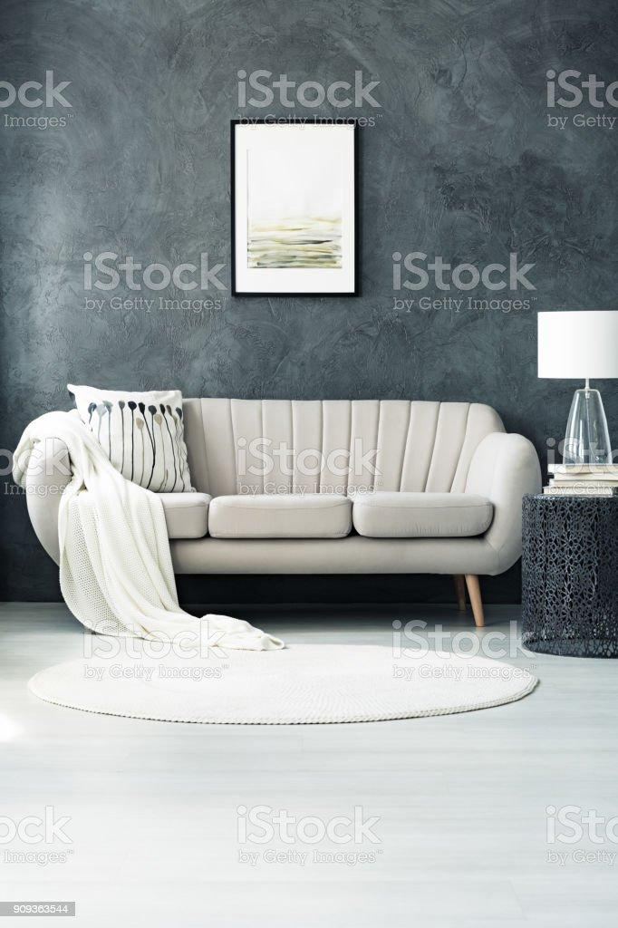 Sofa by dark grey wall stock photo