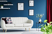 Leather sofa, floral paintings on the blue wall and flower in the vase in a living room interior