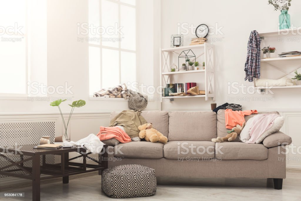 Sofa in messy living room with many stack of clothes. Disorder and...
