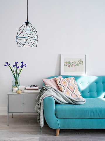 Living room with turquoise sofa and cushions in pink tones, stylish lamp, cabinet decorated with flowers and candles. Day light. Concept of modern lifestyle.