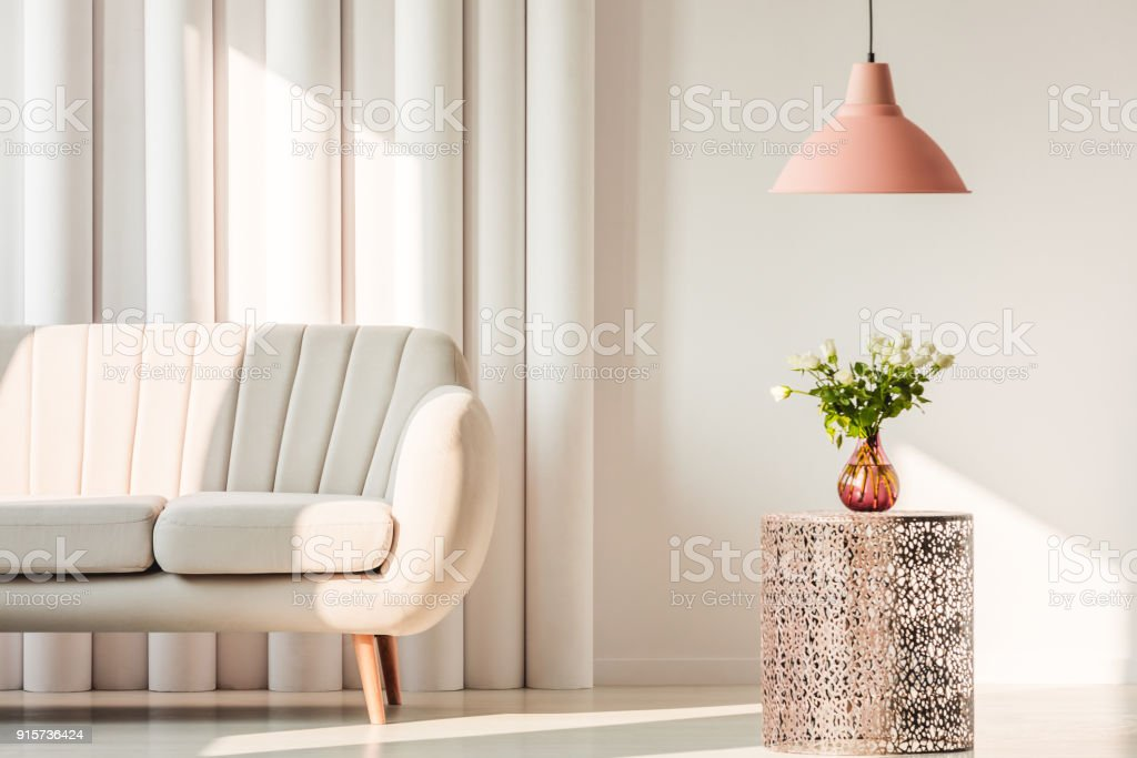 Sofa, lamp and flowers on table