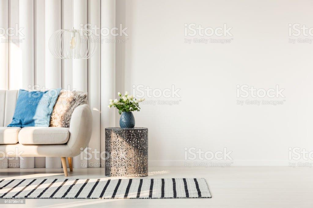 Sofa next to empty wall stock photo