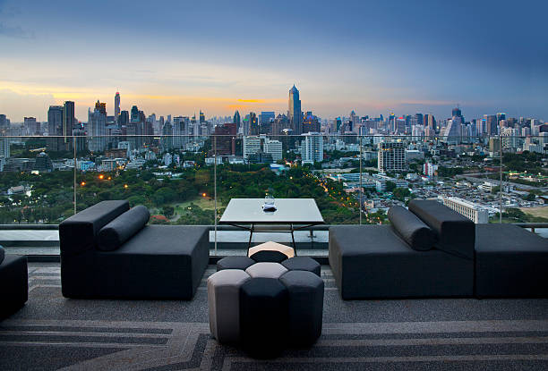 Sofa on terrace overlooking green park and building, Bangkok, Thailand stock photo