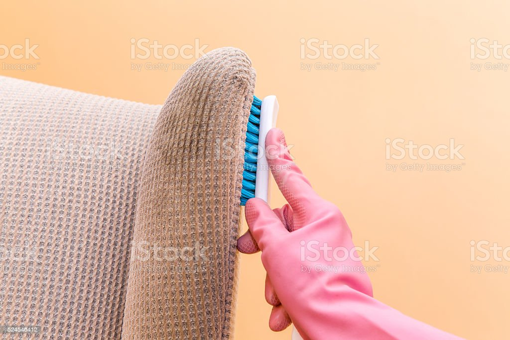 Sofa or armchair chemical cleaning with professionally brush. Spring cleaning. stock photo